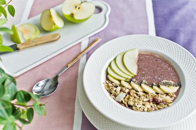 健康的な朝食、バナナ、アップル、チアシード、グラノーラ、ヨーグルトのスムージーボウル。 Premium写真