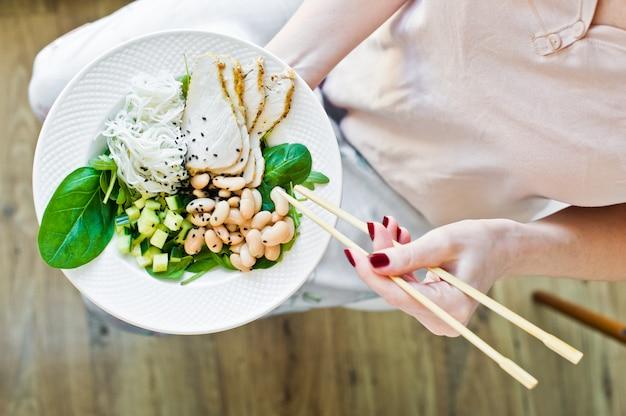 健康的なバランスの取れた食べ物、ガラス麺のサラダ、豆、鶏の胸肉、ほうれん草、ルッコラとキュウリを食べる少女 Premium写真