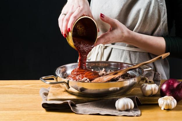 シェフの手がひき肉にトマトペーストを注ぐ Premium写真