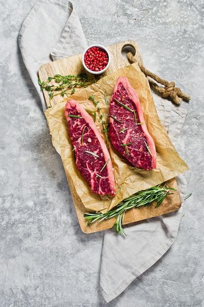 ローズマリーとピンクコショウで木のまな板に牛サーロインステーキ。 Premium写真