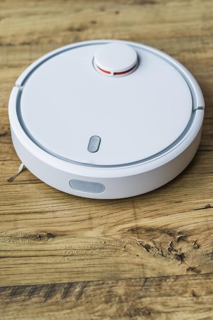 木製の床の上のロボット掃除機。側面図。スマートホームのコンセプトです。自動クリーニング Premium写真