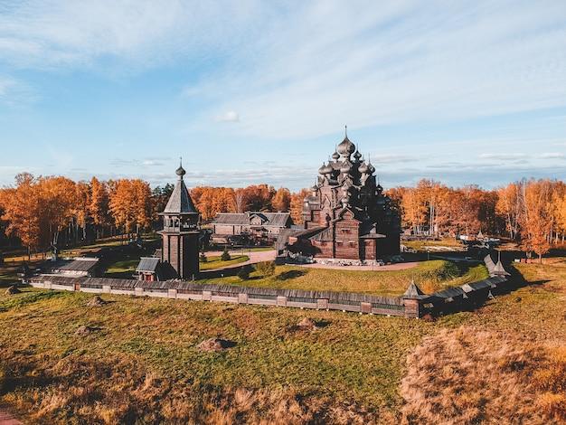 秋の森の古い木造の教会マナー神学者の空撮。ロシア、サンクトペテルブルク。 Premium写真