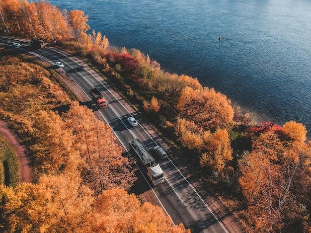 森の朝の光の空撮。カラフルな木々と青い湖の上から、曲がりくねった道。ロシア、サンクトペテルブルク Premium写真