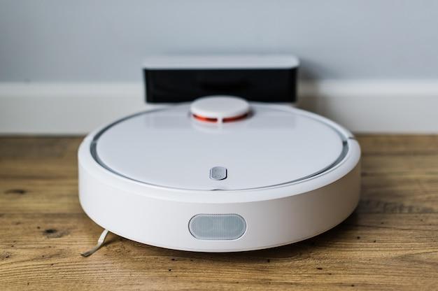 Робот пылесос на деревянный пол. вид сверху. концепция умного дома. автоматическая очистка Premium Фотографии