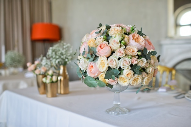レストランでの結婚式のディナー、バラの花瓶で飾られたテーブル。 Premium写真