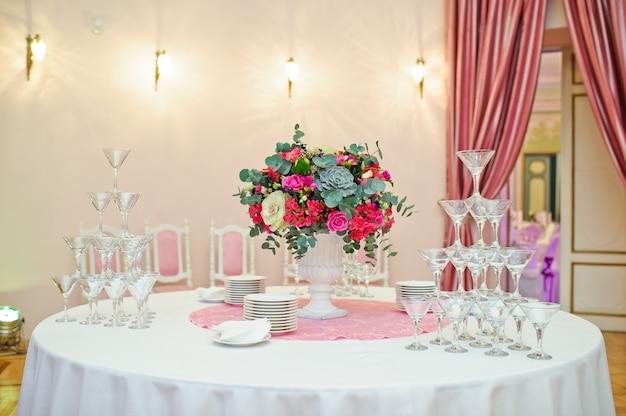 レストランの結婚式の宴会で設定されたテーブル、白いテーブルクロスとナプキンのクラシックなスタイル、花が付いた花瓶。 Premium写真
