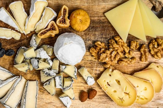 Сырное ассорти с французскими органическими сырами, инжир, орехи на сером фоне. вид сверху. вкусный сырный стартер Premium Фотографии