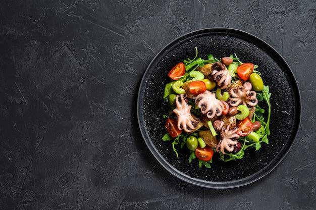タコのグリル、ポテト、ルッコラ、トマト、オリーブのサラダ。黒の背景。上面図。コピースペース Premium写真