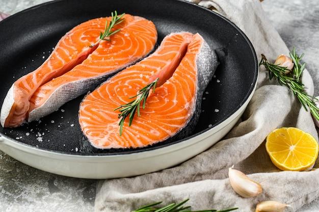 Сырой стейк из лосося в сковороде. здоровые морепродукты. вид сверху Premium Фотографии
