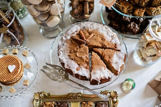 パーティーのためのデザートテーブル。オンブルケーキ、カップケーキ、甘さと花 Premium写真