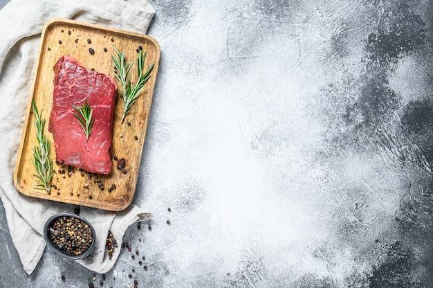 木製トレイの生サーロインステーキ。牛肉。灰色の背景。上面図。テキスト用のスペース Premium写真