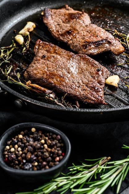 フライパンでサーロインステーキ。グリルされた肉。黒の背景。上面図 Premium写真