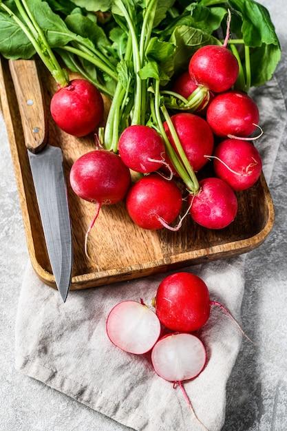 Свежие редиски с вершинами в деревянной миске. ферма органических овощей. серый фон вид сверху Premium Фотографии