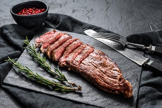 黒い石の板の上に霜降り牛肉のローストステーキ。黒の背景。上面図 Premium写真