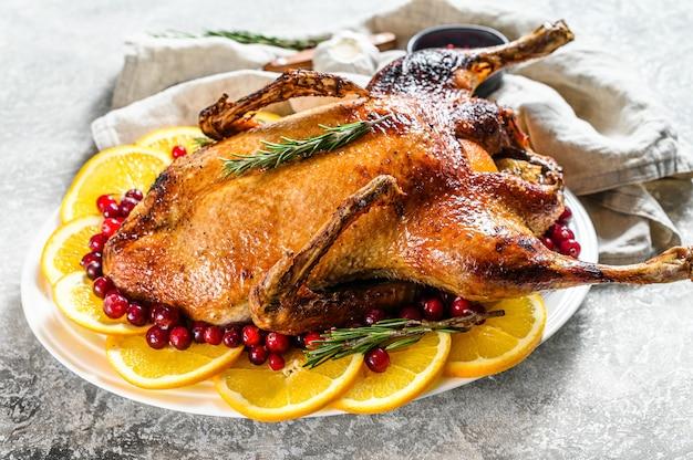 オレンジとローズマリーを詰めた焼き鴨。お祝いテーブル。 Premium写真