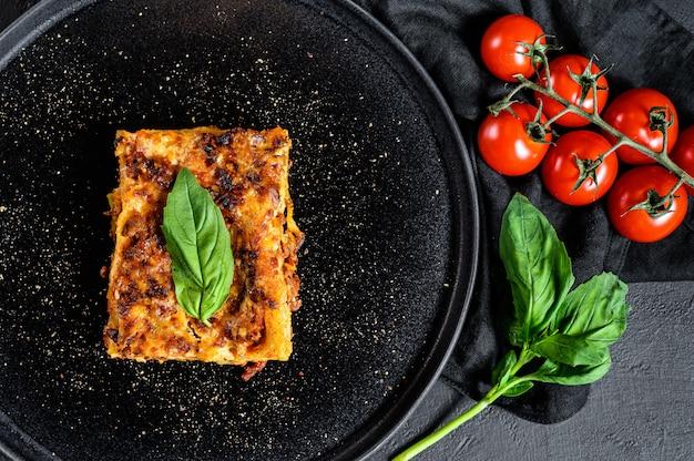 Кусочек вкусной горячей лазаньи. традиционная итальянская кухня. вид сверху Premium Фотографии