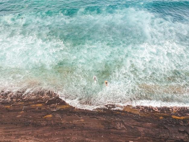 Аэрофотоснимок серферов в волнах атлантического океана. песчаный пляж фон Premium Фотографии