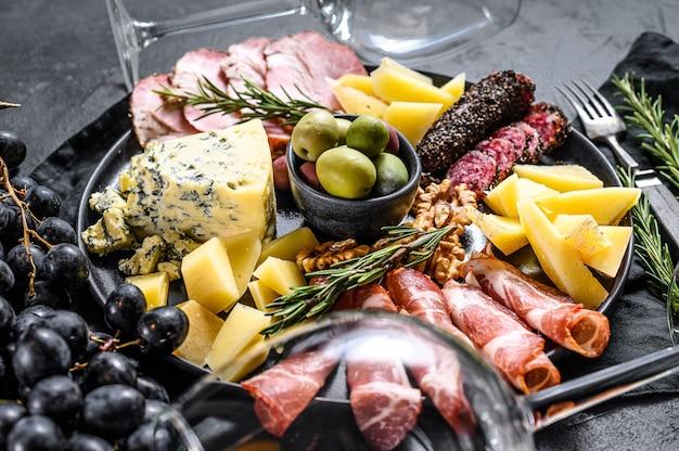 Типичный итальянский антипасто с ветчиной, ветчиной, сыром и оливками. Premium Фотографии