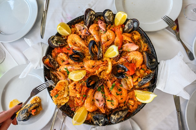Испанское блюдо из паэлья с морепродуктами и свежими креветками, креветками, мидиями, кальмарами, осьминогом и морскими гребешками. подается в сковороде. официант кладет порцию на тарелку. вид сверху. ресторан Premium Фотографии