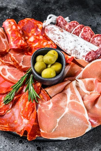 スペインの冷たい肉の品揃え。チョリソ、フエット、ロモ、ハモンイベリコ、オリーブ。上面図 Premium写真