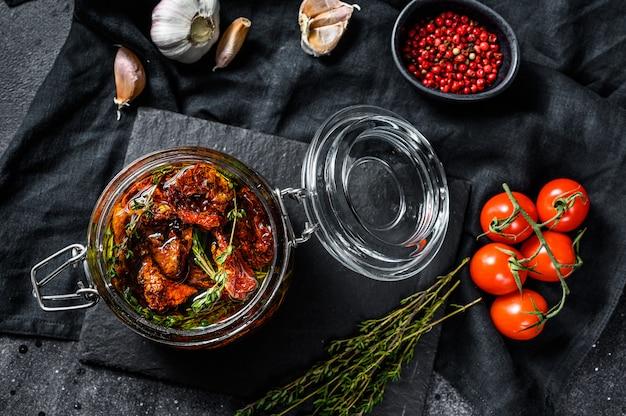 グラスにオリーブオイルにハーブと塩を入れた天日干しトマト。上面図 Premium写真