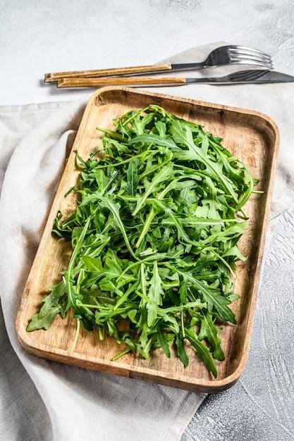 木製のボウルに新鮮なルッコラのサラダ。上面図 Premium写真