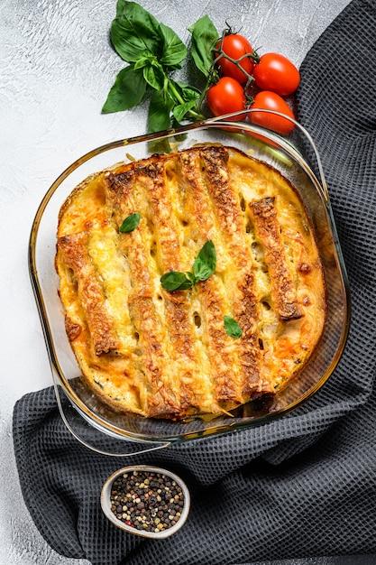 Каннеллони фаршированные соусом бешамель. макароны запеченные с мясом говядины, сливочным соусом, сыром. серый фон вид сверху Premium Фотографии