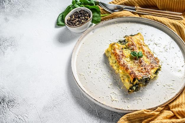 Каннеллони с рикоттой и шпинатом. итальянская кухня. серый фон вид сверху. копировать пространство Premium Фотографии