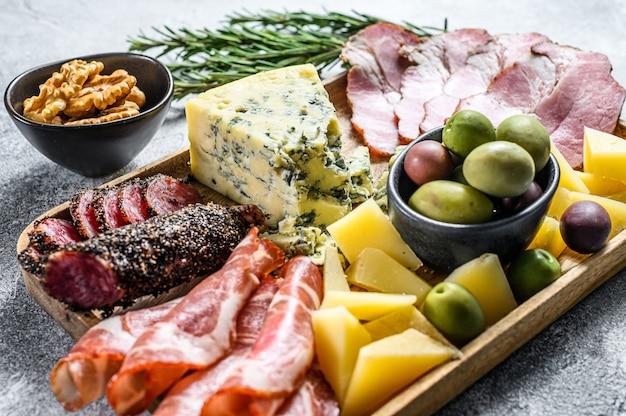 Антипасто с ветчиной, прошутто, салями, голубым сыром, моцареллой и оливками. серый фон вид сверху Premium Фотографии