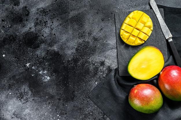 Спелый плод манго, нарезанный кубиками. черный фон. вид сверху. копировать пространство Premium Фотографии