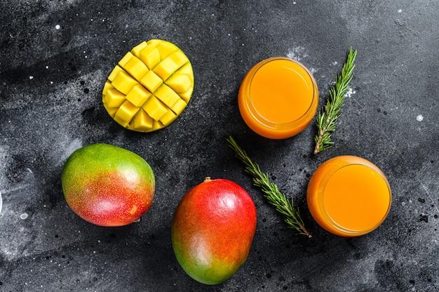 Свежевыжатый сок манго в стакане. черный фон. вид сверху Premium Фотографии
