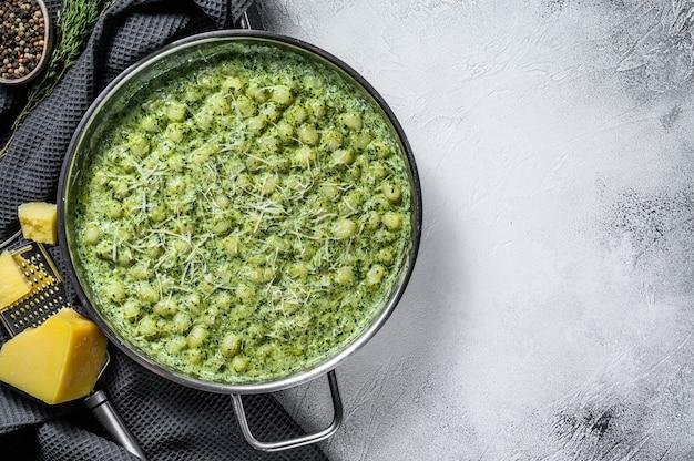 ポテトニョッキ、ペスト、パルメザンチーズ、ほうれん草。イタリアのパスタ。灰色の背景。上面図。コピースペース Premium写真