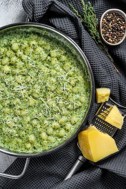 ニョッキとバジルのほうれん草ソース。イタリアンポテトペースト。灰色の背景。上面図。 Premium写真