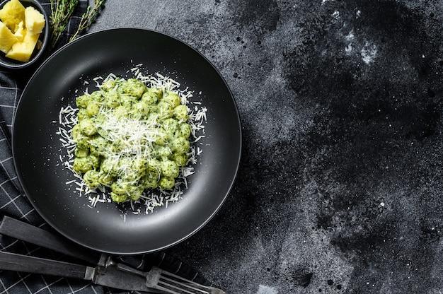 ポテトニョッキ、ペスト、パルメザンチーズ、ほうれん草。イタリアのパスタ。黒の背景。上面図。コピースペース Premium写真