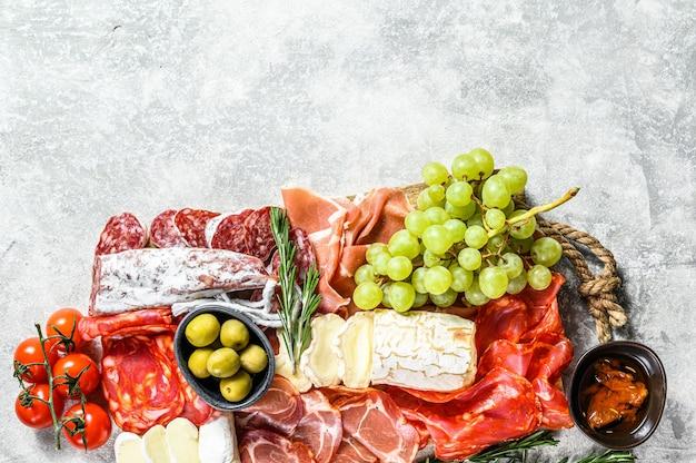 Антипасто ассорти из холодного мяса с виноградом, прошутто, ломтиками ветчины, вяленой говядиной, чоризо салями, фуэтом, камамбером и козьим сыром. серая поверхность. вид сверху. копировать пространство Premium Фотографии