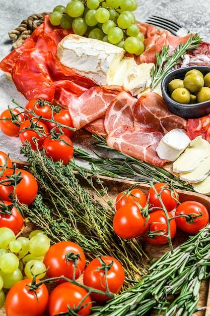Итальянский антипасто, деревянная разделочная доска с ветчиной, ветчиной, пармой, козьим сыром и камамбером, оливками, виноградом. антипаста. серая поверхность. вид сверху Premium Фотографии