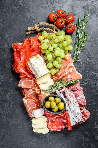 Итальянский антипасто, деревянная разделочная доска с ветчиной, ветчиной, пармой, козьим сыром и камамбером, оливками, виноградом. антипаста. черная поверхность. вид сверху Premium Фотографии