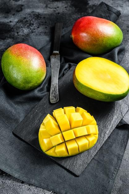 Тропический спелый плод манго. черный фон. Premium Фотографии