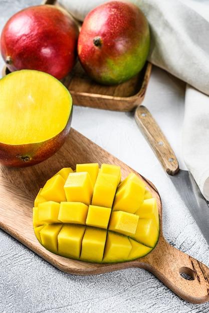 Спелые нарезанные фрукты манго на разделочную доску. серый фон Premium Фотографии