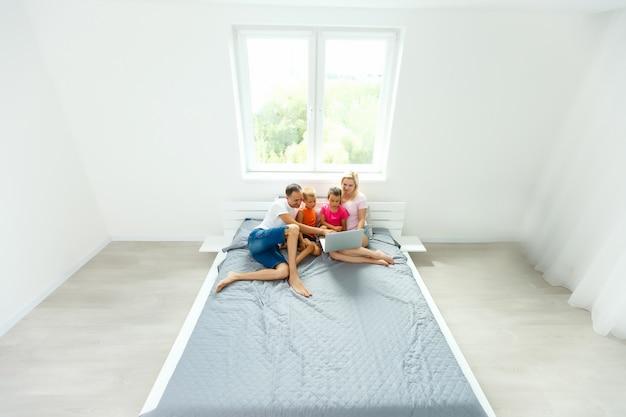 自宅の寝室でラップトップを使用してベッドの上の幸せな家族 Premium写真
