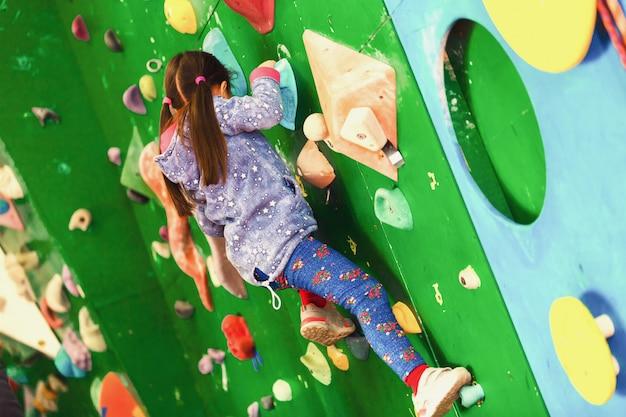 屋内の実用的な壁に登っている女の子 Premium写真