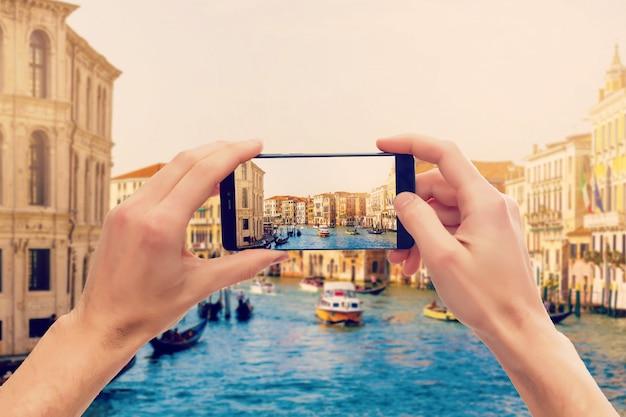 グランドキャナルのゴンドラでモバイルスマートフォンで写真を撮る Premium写真