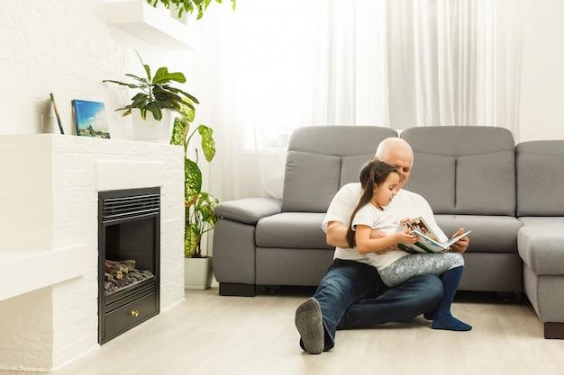 祖父の家で物語の本を読んで幸せな少女 Premium写真
