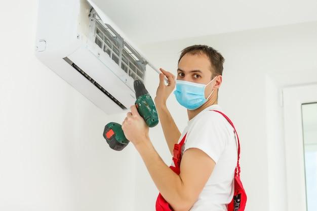 室内のエアコンを掃除する男性技術者 Premium写真