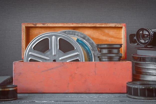木製の箱、レンズおよび古い映画カメラのフィルムが付いている巻き枠 Premium写真