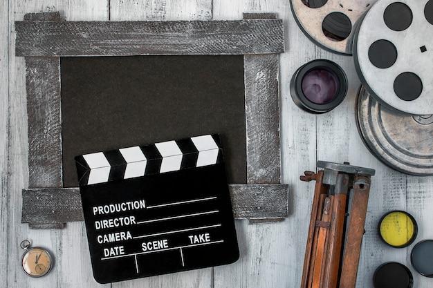 カチンコ、フィルムのリール、三脚 Premium写真