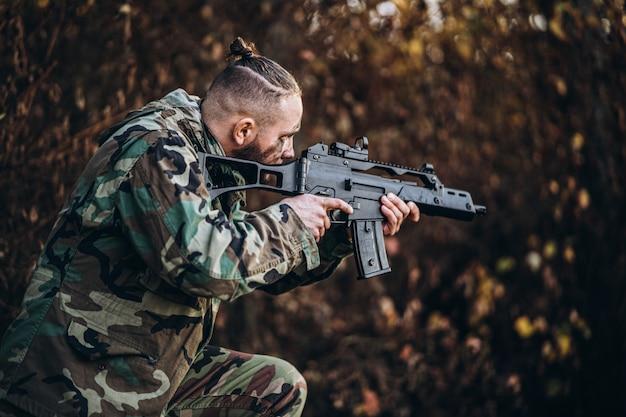 ライフルとエアソフトフォレストで野外で遊ぶ塗装面を持つ兵士をカモフラージュします。 Premium写真