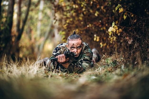 ライフルとライフルを目指して草に横たわっている塗装面を持つ兵士をカモフラージュします。 Premium写真