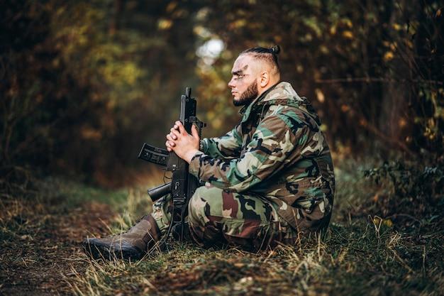 ライフルと草の中に座って塗装面を持つ兵士をカモフラージュします。 Premium写真