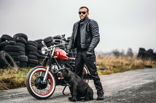 革のスーツを着たバイカーと彼の犬は、道路上の赤いバイクの近くに立っています。 Premium写真